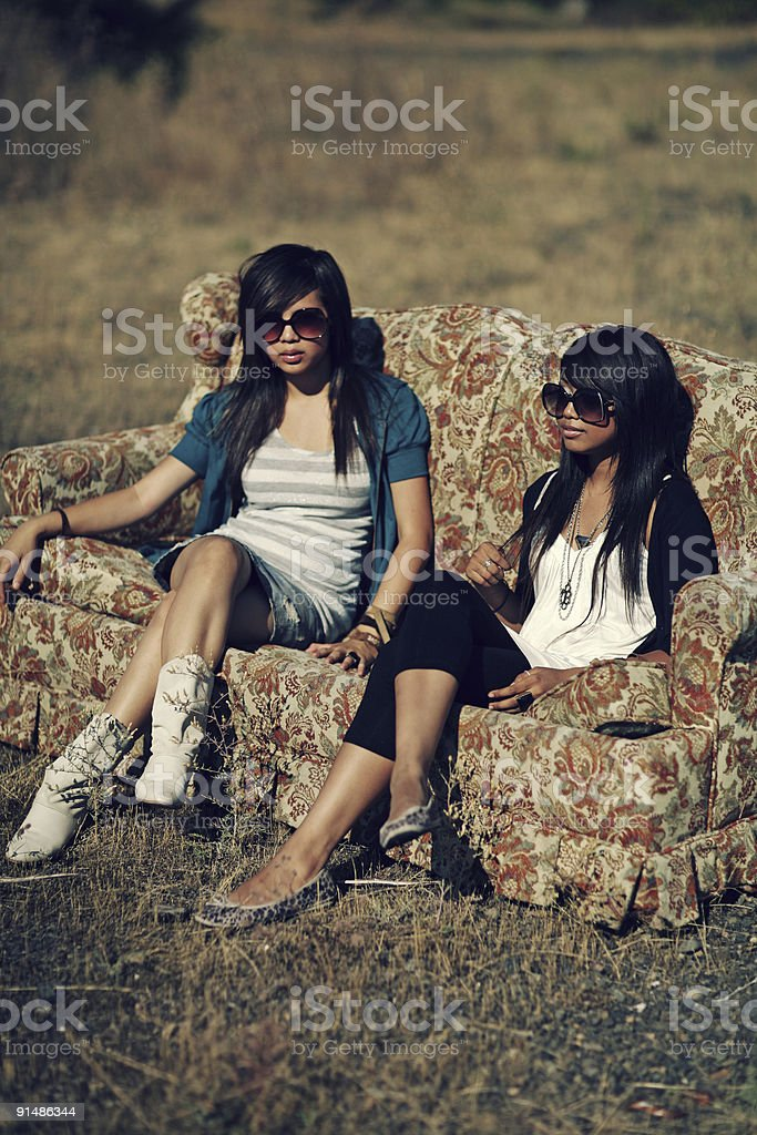 Two Girls Sitting on Old Couch Outdoors