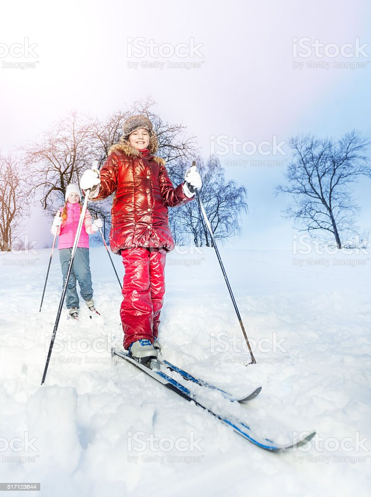Two girls slide downhill on skies at a winter day stock photo