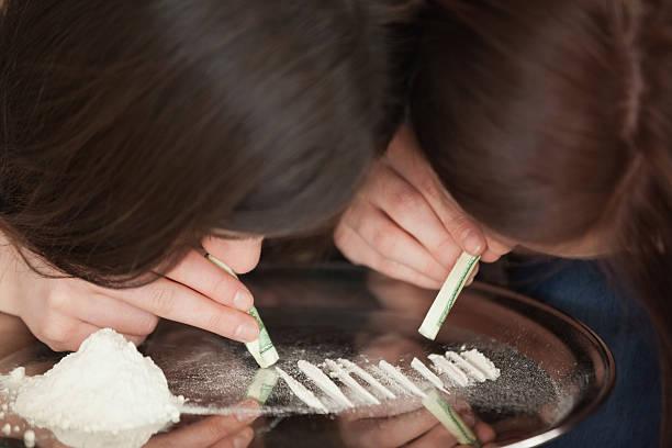 two girls snorting an illegal white powder - ketamine stockfoto's en -beelden