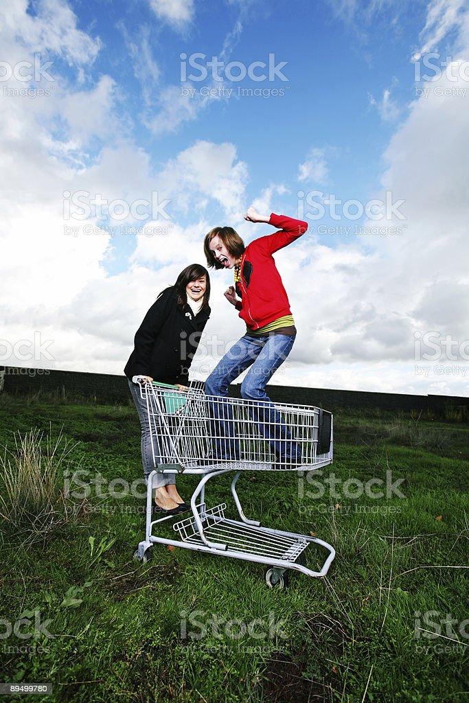 Due ragazze su carrelli acquisti in campo foto stock royalty-free