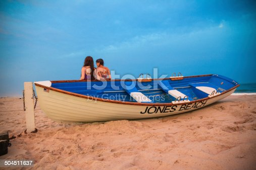 Two girls stay at the Jones Beach next to the boat