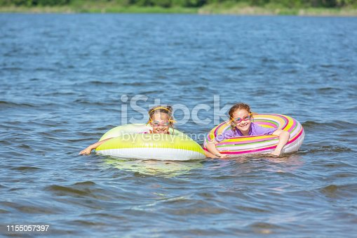 Two young girls (sisters) playing in innertube float toys on a lake in summer. The younger sister is on the right, with the older sister on the left. Both girls are wearing swim goggles and rash guard swim shirts. Taken on a beautiful summer day. In this image the girls are side by side and smiling at the camera.