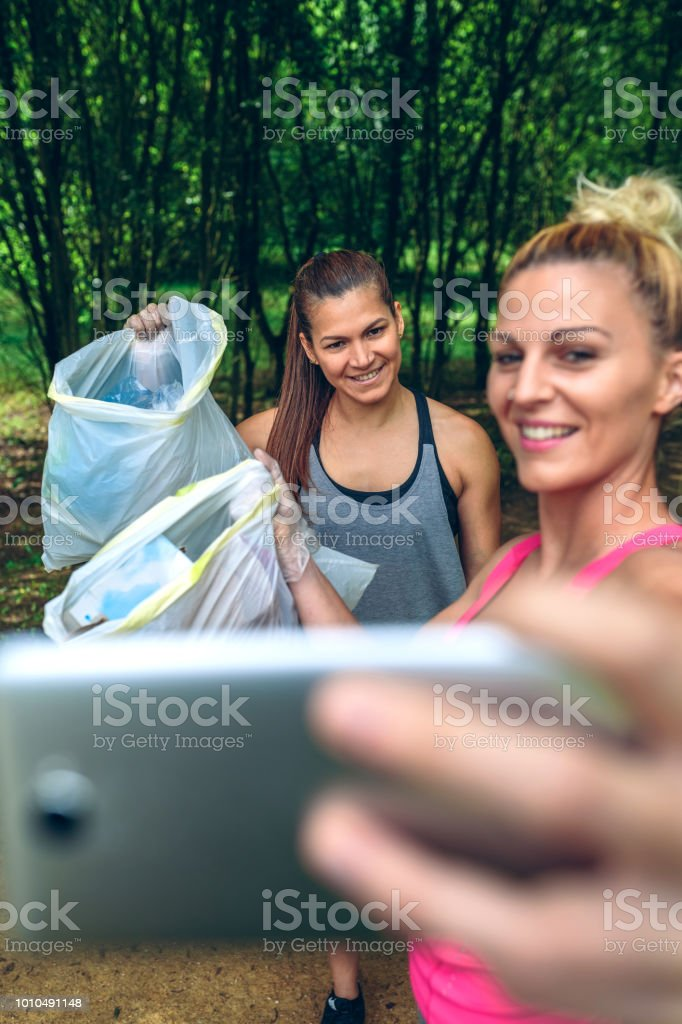 Two girls taking a selfie after plogging stock photo