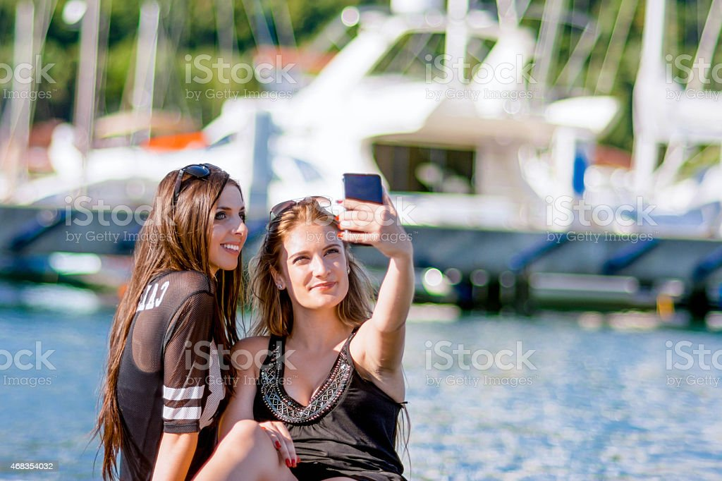Two girls taking a selfie at a marina stock photo