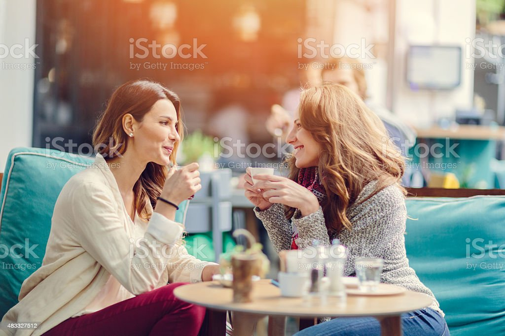 Two girls talking in a cafe stock photo