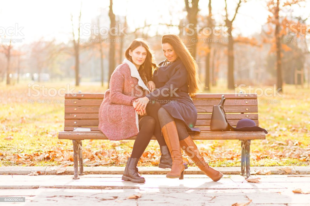 Two girls talking in the park stock photo