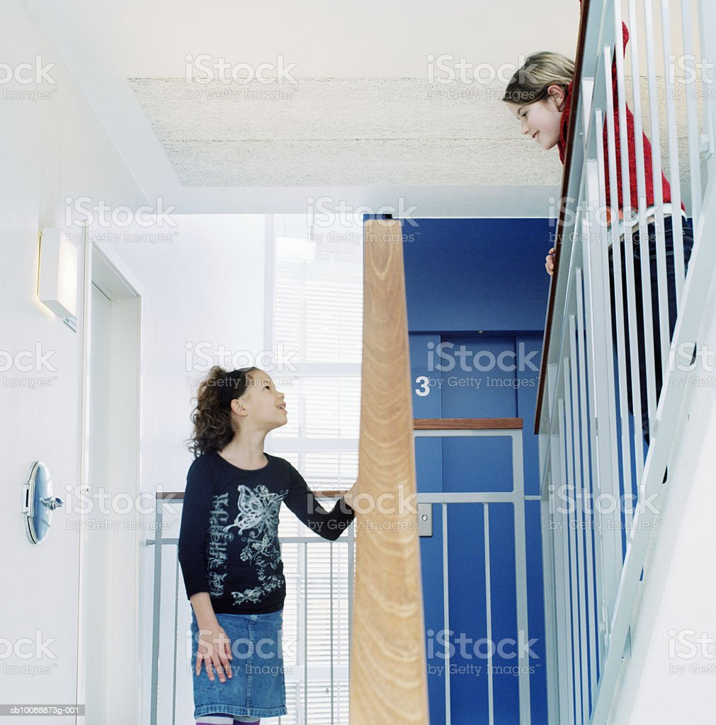 Two girls (8-11) talking on staircase foto de stock royalty-free