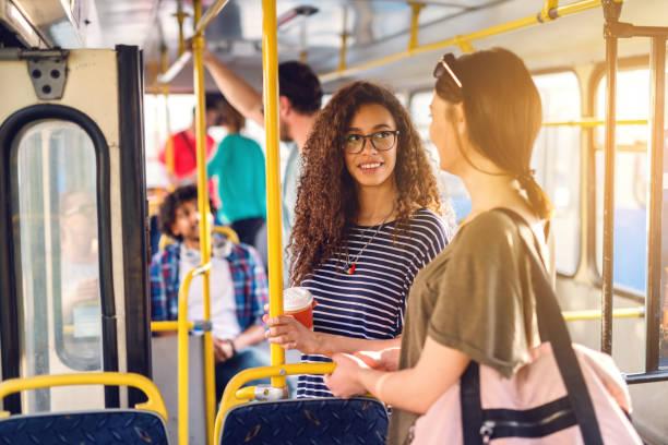 zwei mädchen talking beim warten auf den bus zu bewegen. - tour bus stock-fotos und bilder