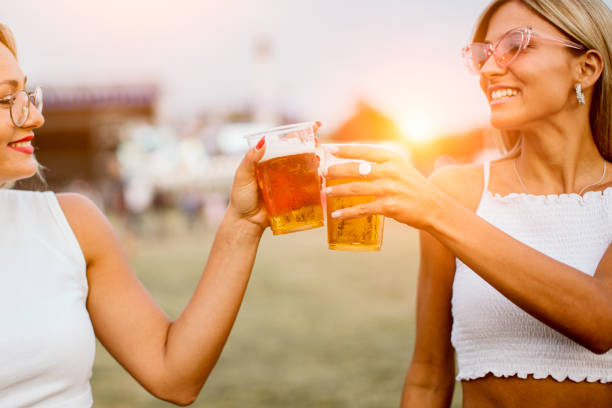 Two girls toasting with beer at music festival stock photo