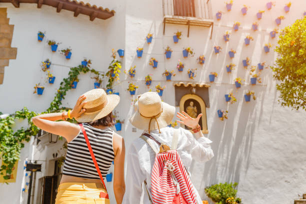 Two girls tourist admiring great view of flowerpots on the white walls on famous Flower street in Andalusia Two girls tourist admiring great view of flowerpots on the white walls on famous Flower street in Andalusia southern charm stock pictures, royalty-free photos & images