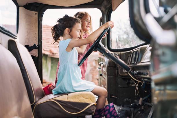 zwei mädchen versucht, einen alten lkw zu fahren - alte wagen stock-fotos und bilder