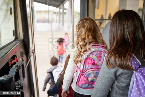 1031397608 istock photo Two girls waiting behind their friends to get off school bus 1031397114