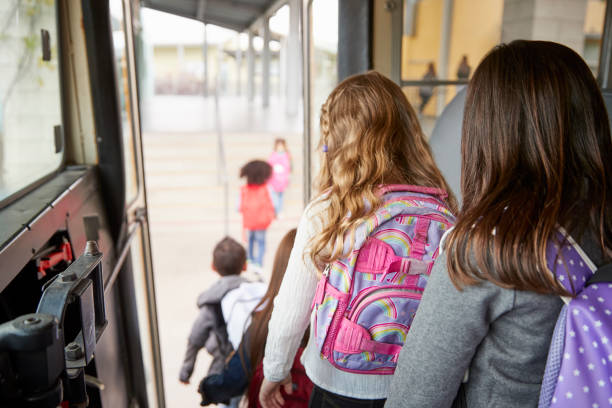 two girls waiting behind their friends to get off school bus - school buses stock pictures, royalty-free photos & images