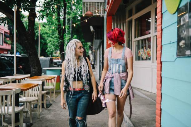 two girls walking down the street - showus стоковые фото и изображения