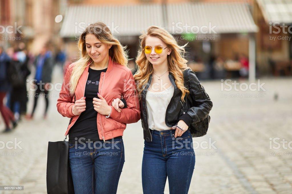 6fd4a4dcc0 Dos chicas caminando por la calle de la ciudad y hablar foto de stock libre  de