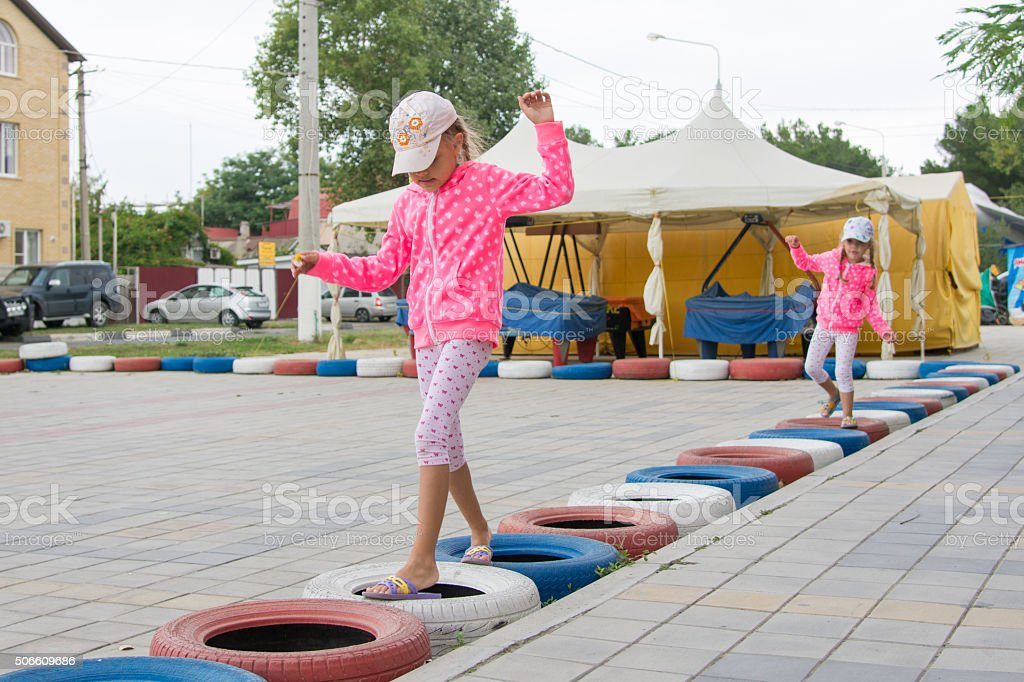 Two girls walking with interest on tires protecting circuit stock photo