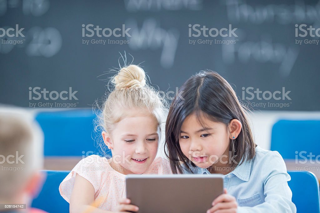 Two Girls Watching a Video on a Digital Tablet stock photo
