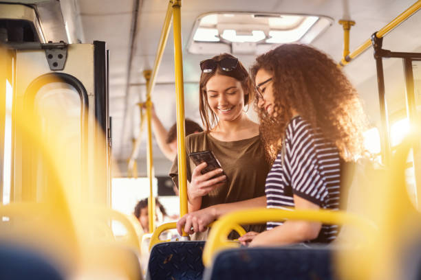 two girls watching phone and smiling while standing on a bus. - montare foto e immagini stock