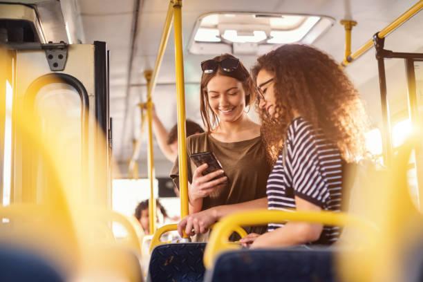 dos chicas ver teléfono y sonriendo mientras está parado en un autobús. - autobús fotografías e imágenes de stock