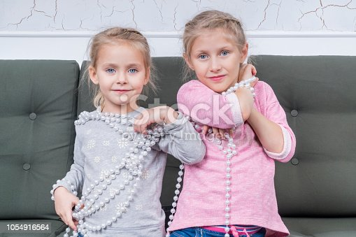 Two sisters sitting on the couch trying on a necklace of white pearl beads