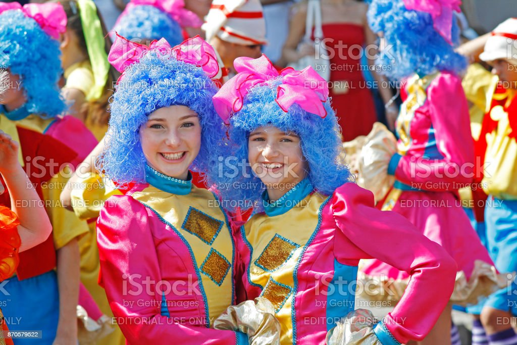 Two Girls Wearing Bright Costumes And Blue Wigs In Carnival Parade