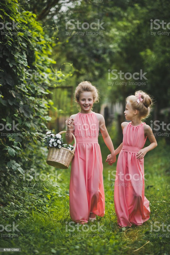 Two girls with a basket of flowers and a stroll in the garden 65 royalty-free stock photo