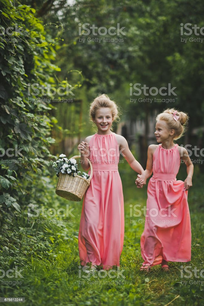 Two girls with a basket of flowers and a stroll in the garden 6579. royalty-free stock photo