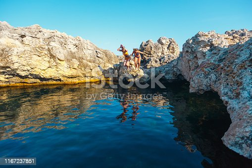 Two girls with a camera jump into the sea water from a cliff.