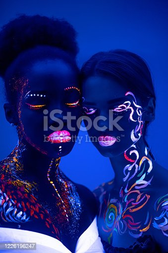 istock two girls with fluorescent make-up isolated 1226196247