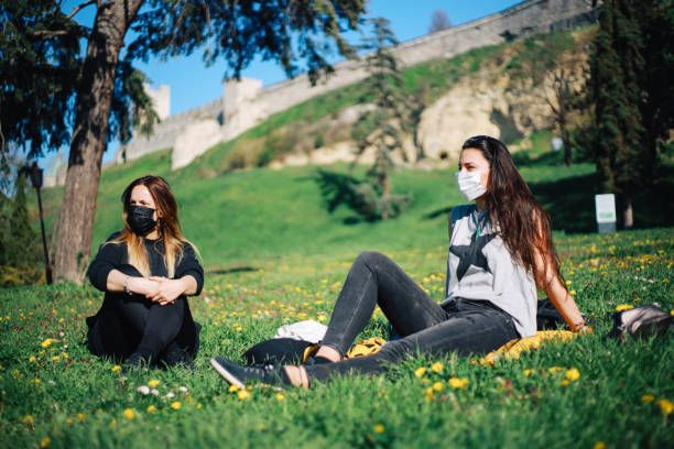 Two girls with masks in the park during pandemic stock photo