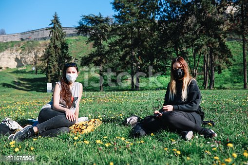 Two young women with protective masks hanging out in the park during the coronavirus outbreak.