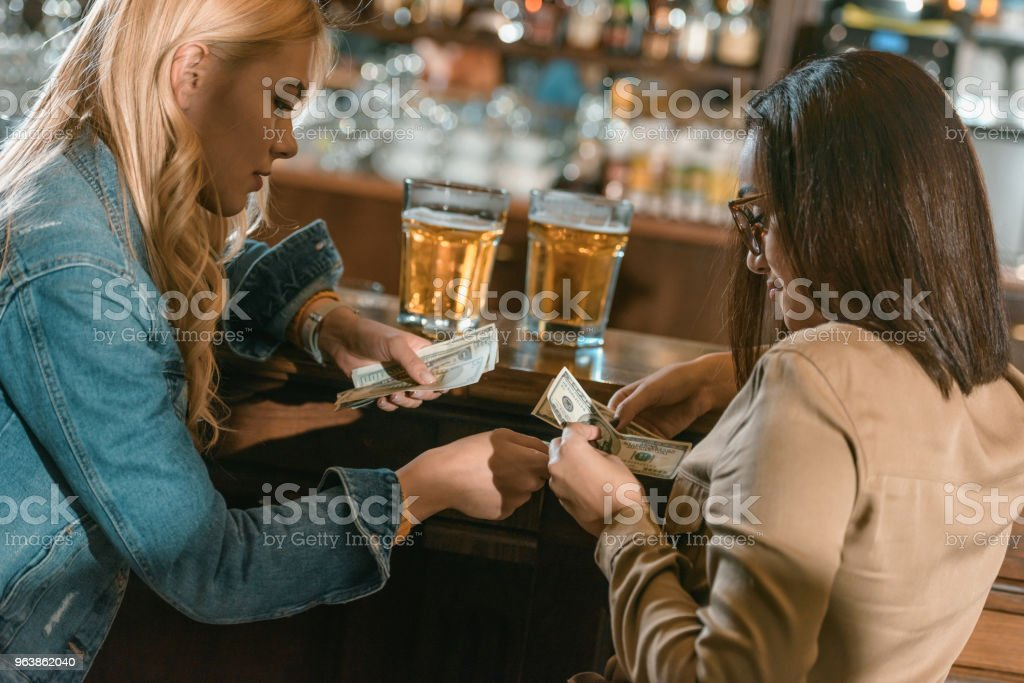 two girls with money paying for drink at bar - Royalty-free Adult Stock Photo