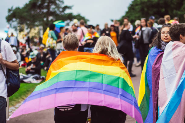 Two girls with rainbow flag  in Kaivopuisto garden Helsinki, Finland - June 30, 2018: Two girls with rainbow flag  in Kaivopuisto garden on Helsinki pride festival lgbtqi rights stock pictures, royalty-free photos & images