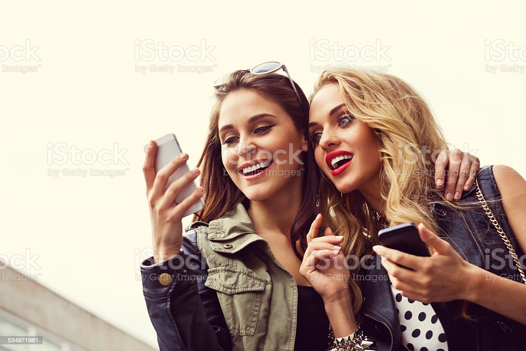 Two girls with smartphone against sky Two happy friends using smart phones outdoor. Close up of faces. 20-24 Years Stock Photo