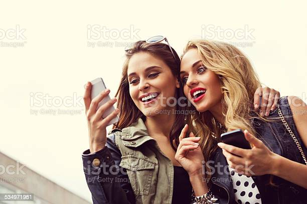 Two Girls With Smartphone Against Sky Stock Photo - Download Image Now