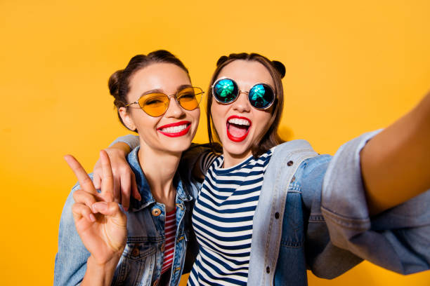 two glad positive grinning lady stand in glasses spectacles street style stylish trendy cool casual denim jeans clothes isolated on yellow background in take picture on cellular make hollywood smile - amici foto e immagini stock