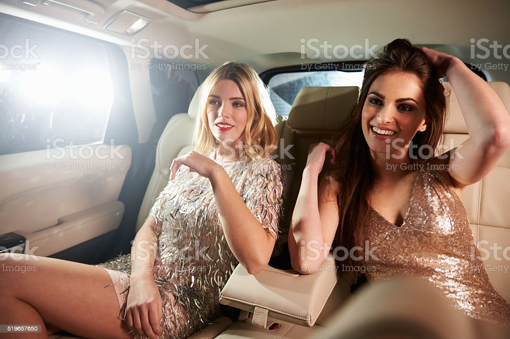 Two glamorous women relax in the back of a limo, in stock photo
