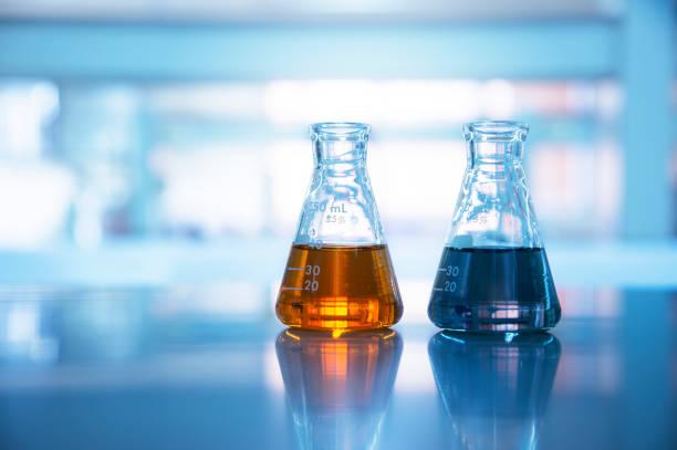 dos frascos de vidrio con solución naranja y negro en el fondo de laboratorio de ciencias químicas - química fotografías e imágenes de stock