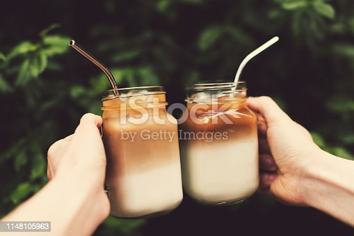 Two glass jars of ice coffee metal straws in woman and man hands. Clink cups of coffee.  Outdoor shot. Lifestyle, picnic vibes. Trendy toning. Copy space for your text.