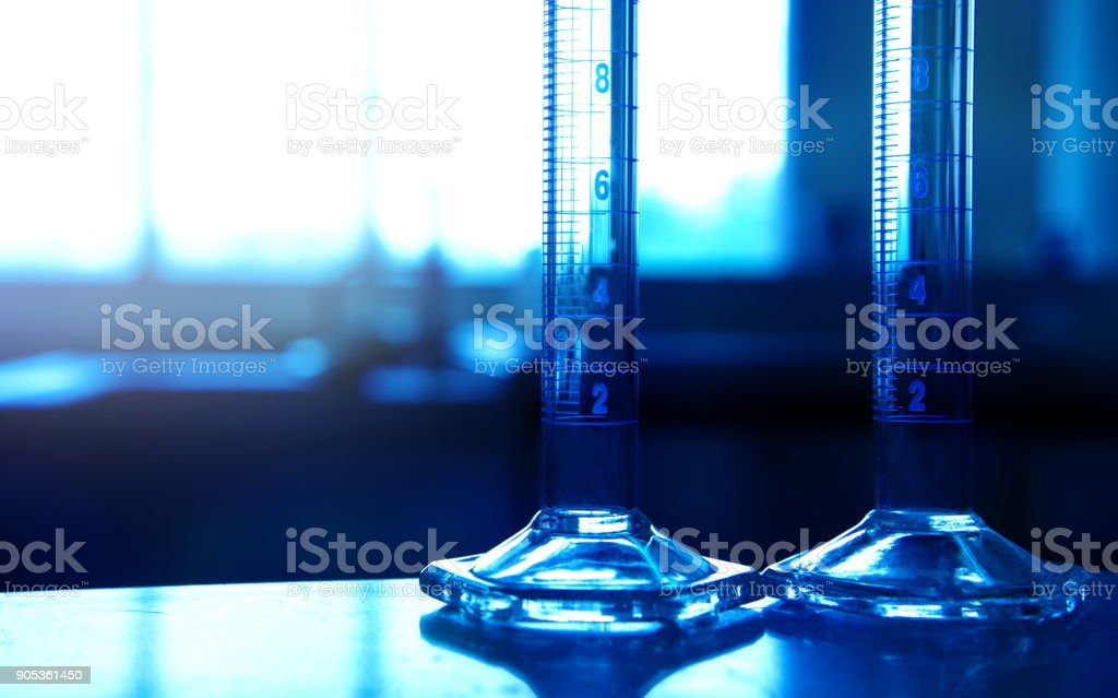 two glass measuring cylinders in chemical science technology laboratory background stock photo