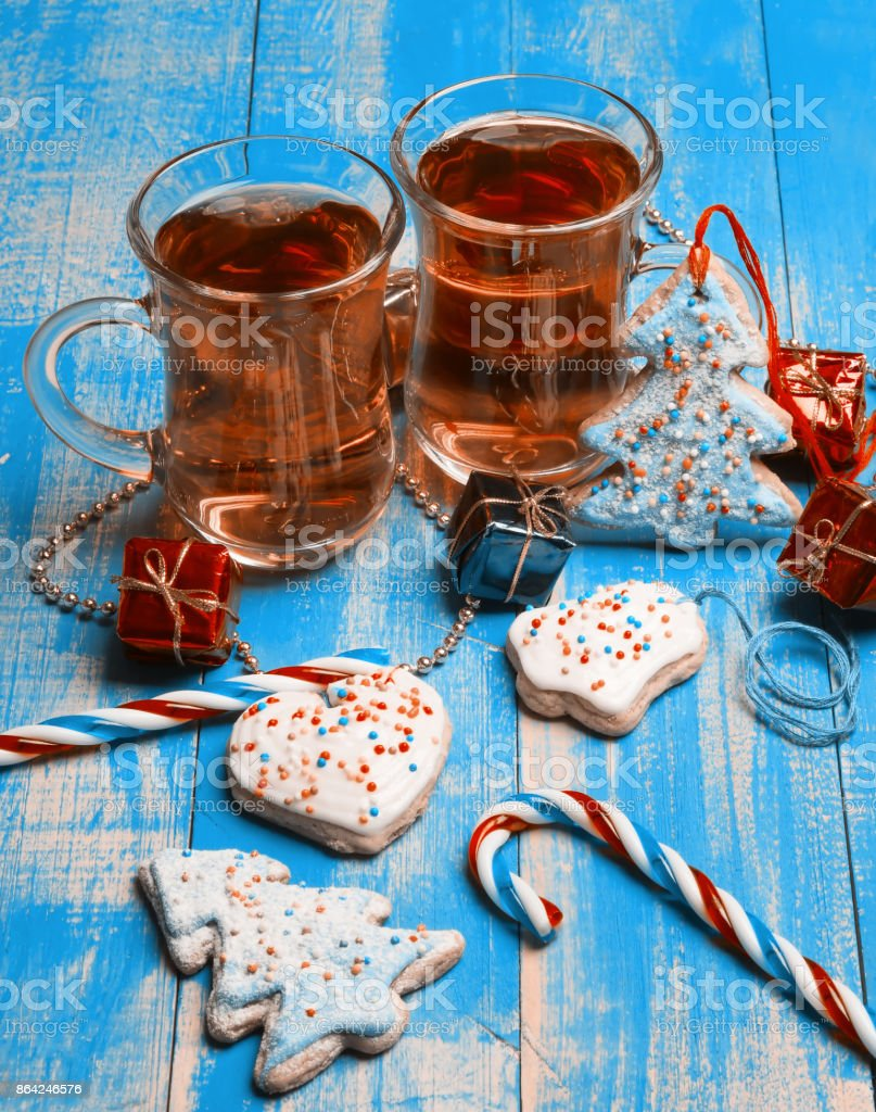 Two glass mugs of tea, gingerbread and candy canes on a blue background. royalty-free stock photo