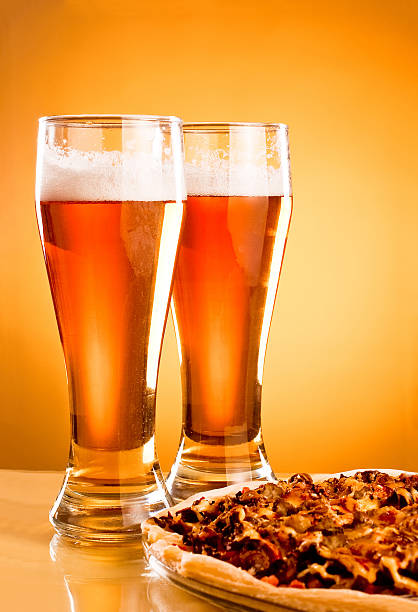 two glass of beer and pizza over yellow background - dikke pizza close up stockfoto's en -beelden