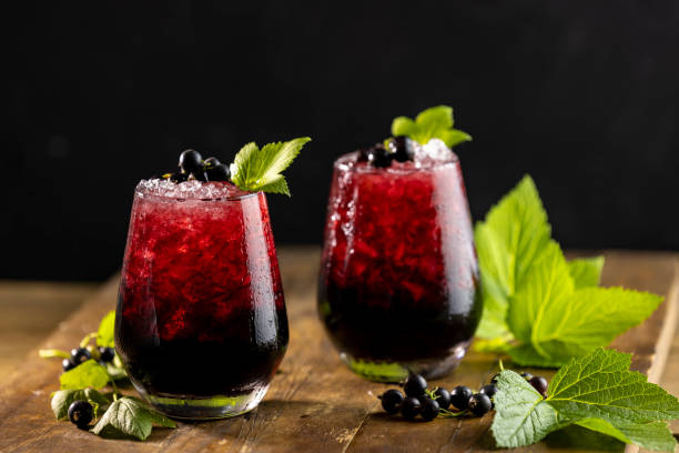 Two glass of cold ice black currant juice or cocktail with ripe stock photo