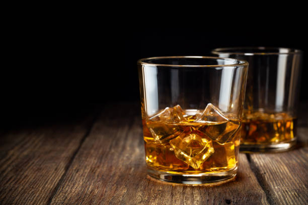 Two glass of whiskey with ice Two glass of whiskey with ice on wooden table. Copy space for text. brandy stock pictures, royalty-free photos & images