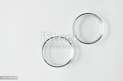 Two glass petri dish with transparent gel with air bubbles and one empty on white background, top view and copy space. Concept laboratory tests and research, making cosmetic