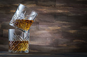 Close up shot of a tumbler glass with whiskey on the rocks.