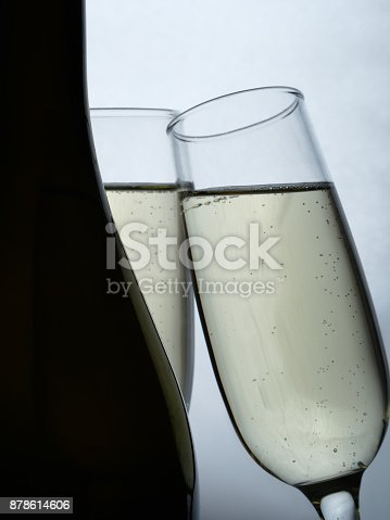 1073474208 istock photo Two glasses and a bottle of champagne on a white background. 878614606