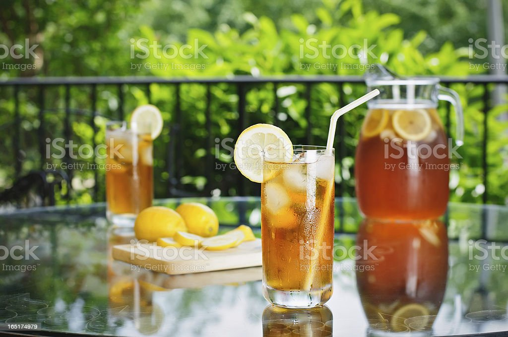 Two glasses and a drink pitcher of ice tea outdoors stock photo