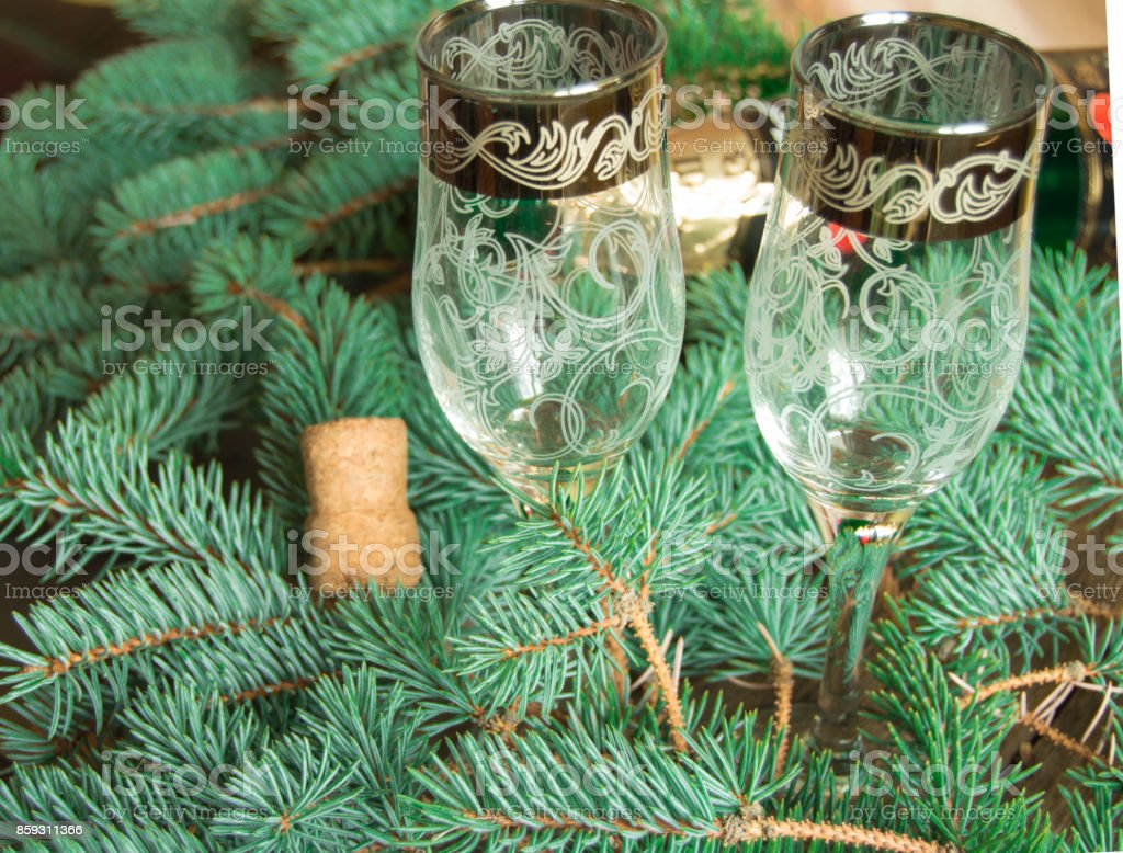 two glasses are on the background of fir branches with a bottle of champagne and cork, blurred background stock photo