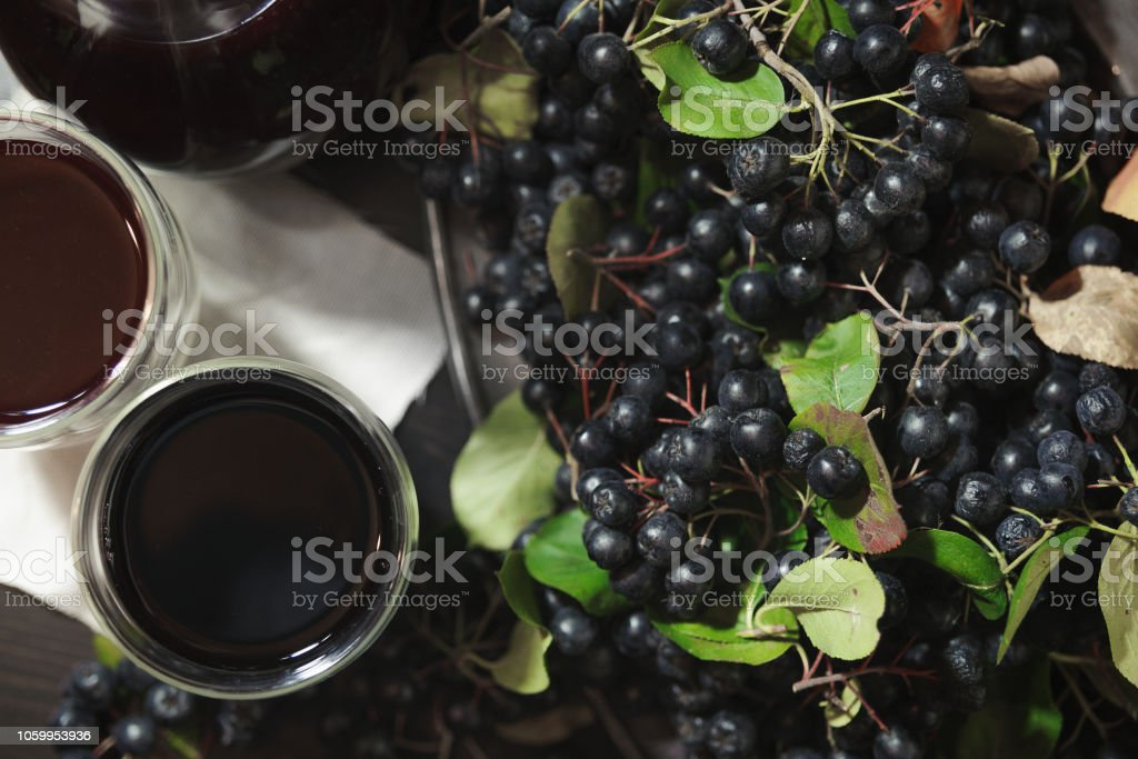 Two glasses fresh juice from black chokeberry berries ( Aronia melanocarpa ) near branches with black berries. Top view. – zdjęcie